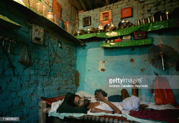 Resutia tuberculosis patient being treated by operation ASHA looks up while lying on his bed in a room where him and five other family members live...
