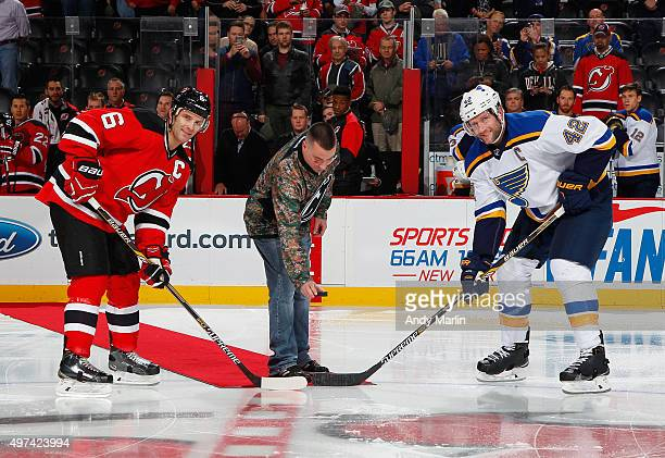 Ret USMC Sergeant John Kelly drops the ceremonial first puck between Andy Greene of the New Jersey Devils and David Backes of the St Louis Blues to...