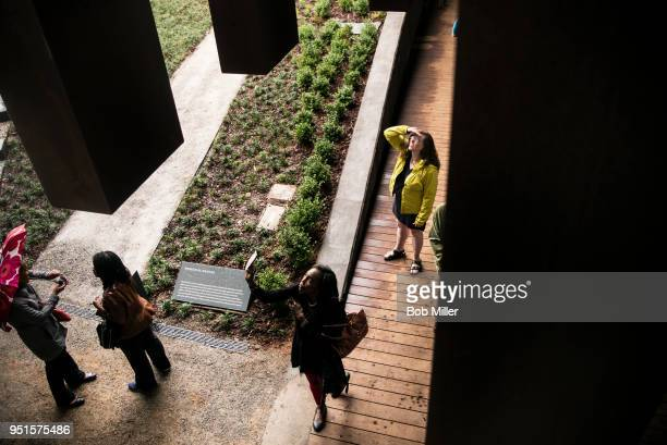 Reta Miles takes photographs at the National Memorial For Peace And Justice on April 26, 2018 in Montgomery, Alabama. The memorial is dedicated to...
