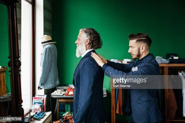 retail assistant fitting suit jacket to customer - tailor stock pictures, royalty-free photos & images