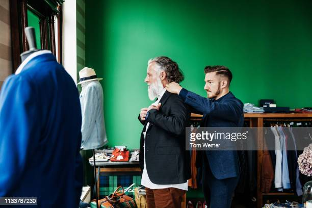 retail assistant helping customer trying on a jacket - jacke stock-fotos und bilder