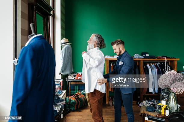 retail assistant helping customer with shirt - menswear ストックフォトと画像