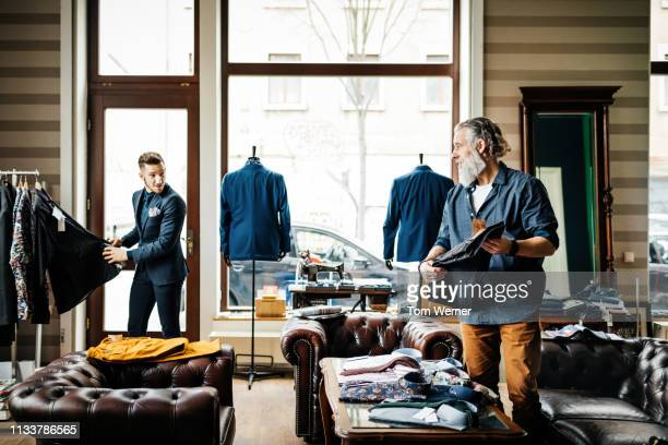 retail assistant helping man in menswear store - leather shirt stock pictures, royalty-free photos & images