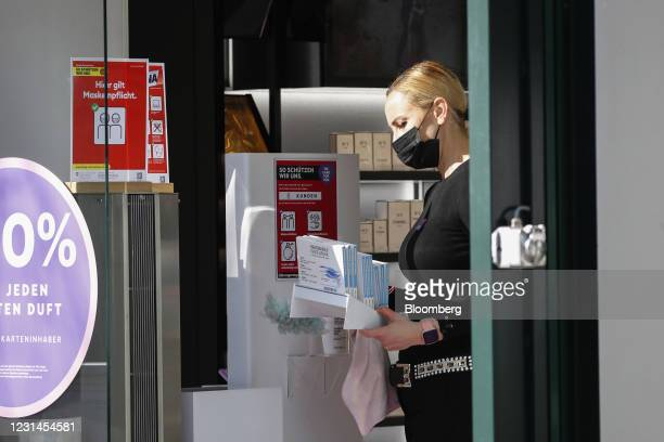 Retail assistant prepares face masks at the entrance to a cosmetics store in Zurich, Switzerland, on Monday, March 1, 2021. Switzerland has allowed...