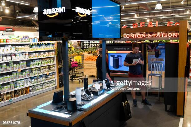 Retail consultant Matt Bailey helps customer Geoff Witherspoon at the Amazon PopUp in the Union Station Whole Foods on Thursday March 22 2018 Amazon...