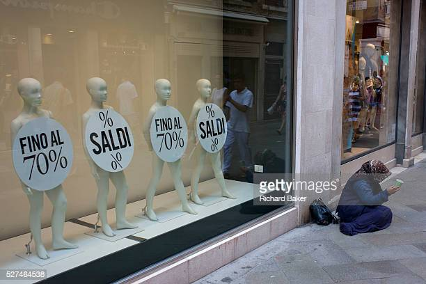 Retail mannequins advertising a 70% sale with a woman street beggar in the San Marco shopping district of Venice Italy The four little people...