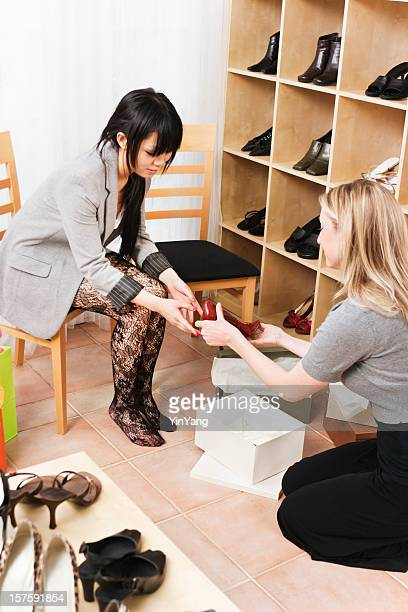 retail sales clerk and customer in boutique shoe store vt - stocking feet stock photos and pictures
