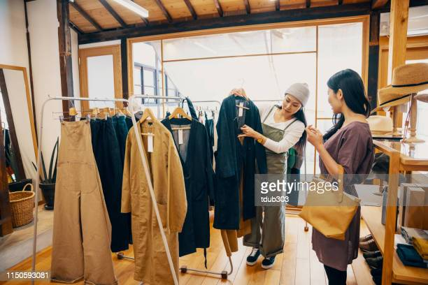 retail shop clerk helping a mid adult woman customer shop for clothing in a boutique - assistant stock pictures, royalty-free photos & images