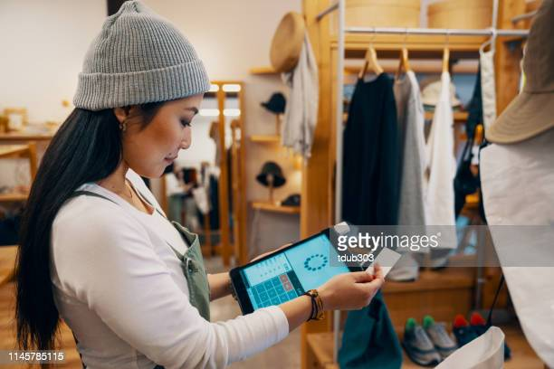 retail shop clerk taking a mobile credit card payment on a digital tablet - e commerce stock pictures, royalty-free photos & images