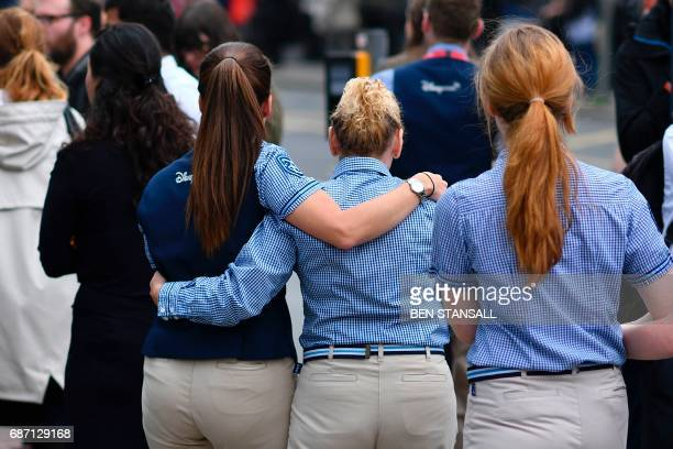 Retail staff hug each other after being evacuated from the Arndale Centre shopping mall in Manchester northwest England on May 23 2017 following a...