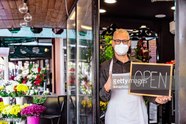 retail store owner standing in front of the entrance - small stock pictures, royalty-free photos & images
