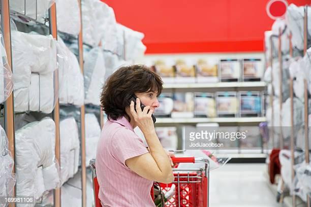 Einzelhandel: Frau Kauf Kissen und am Telefon