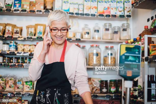 retail woman using mobile phone at the healthy food store - working seniors stock pictures, royalty-free photos & images