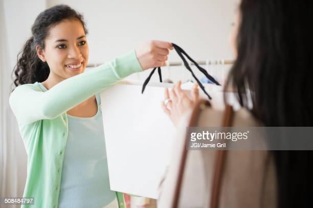 Retail worker handing shopping bag to customer