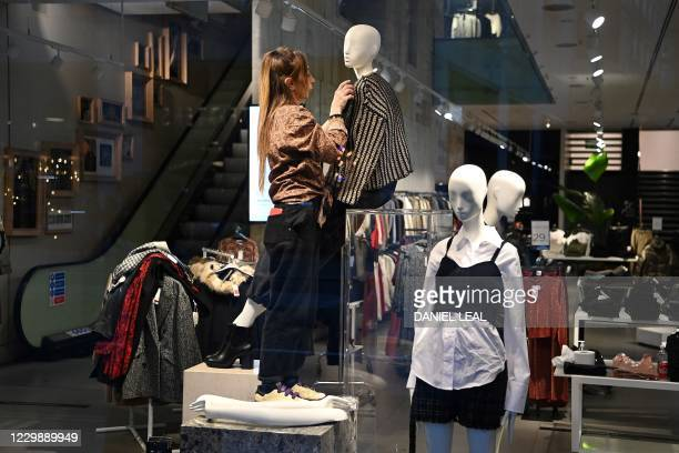 Retail worker helps to prepare stock in a clothes shop in London on December 1 as non essential retailers get ready to reopen following a second...