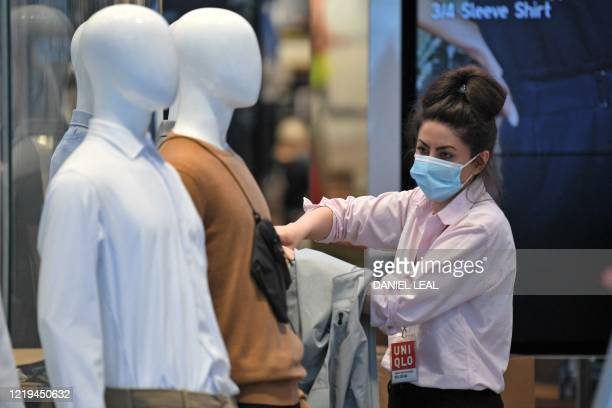 Retail worker wearing PPE , including a face mask as a precautionary measure against COVID-19, works in the window display of a UNIQLO clothes store...