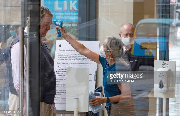A retail worker wearing PPE of a face mask or covering as a precautionary measure against spreading COVID19 takes the temperature of a customer...