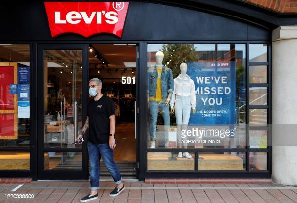 A retail worker wearing PPE of gloves and a face mask or covering as a precautionary measure against COVID19 directs customers waiting to enter a...
