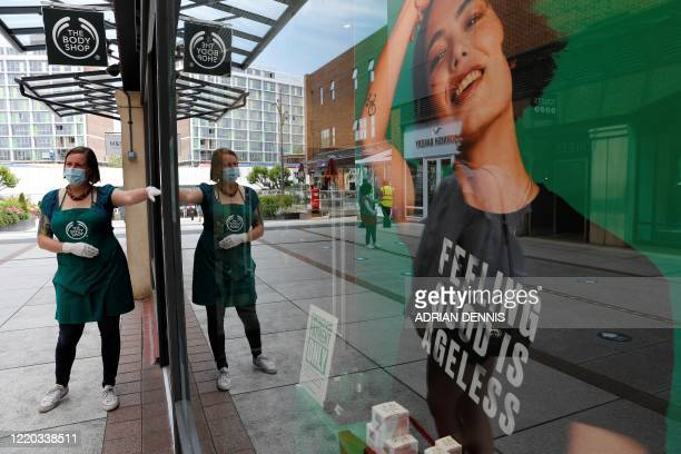 Retail worker wearing PPE , of gloves and a face mask or covering as a precautionary measure against COVID-19, directs customers waiting to enter a...