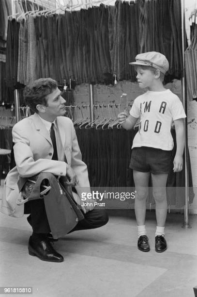 Retailer John Stephen with a young customer 5yearold Howard Raymond the son of club owner Paul Raymond at his London store April 1965 Howard is...