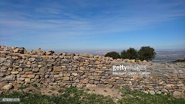 Retaining Stone Wall On Mountain Against Blue Sky