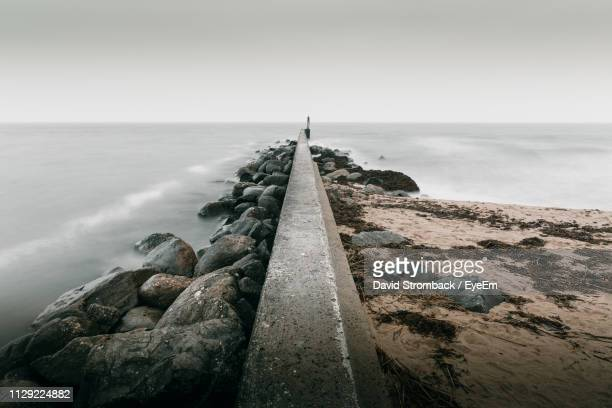retaining wall at beach against sky - retaining wall stock pictures, royalty-free photos & images