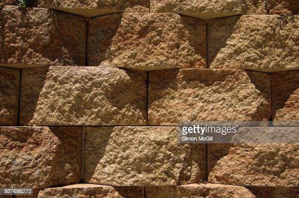 retaining wall made from textured interlocking bricks - retaining wall stock pictures, royalty-free photos & images