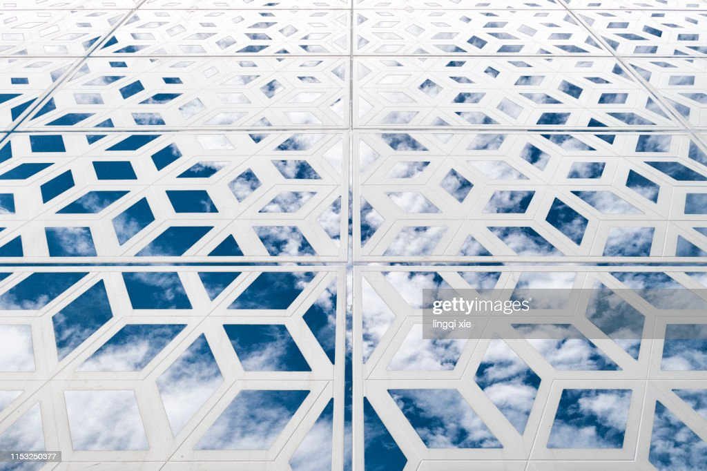 Reticulated cube structure under blue sky and white clouds : Stock Photo
