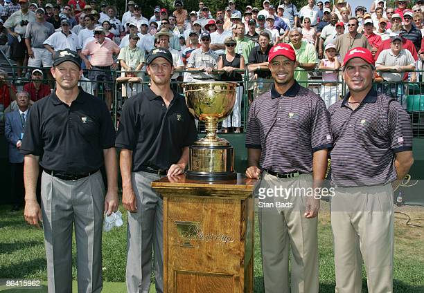 Retief Goosen and Adam Scott of the International team and Tiger Woods and Fred Couples of the US team pose with the Presidents Cup before teeing off...