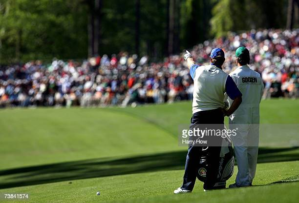 Retief Goosen of South Africa chats with his caddie Colin Byrne on the 13th hole during the final round of The Masters at the Augusta National Golf...