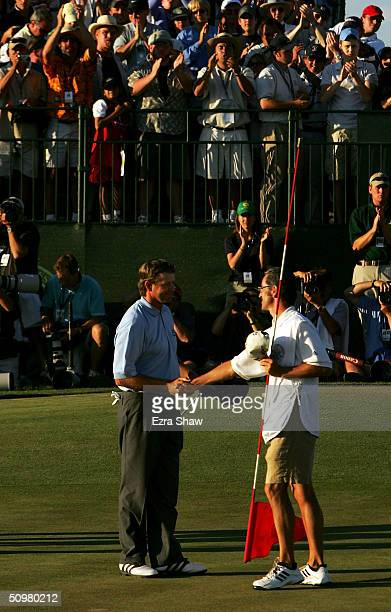 Retief Goosen of South Africa is congratulated on the 18th green by caddie Colin Bryne after winning the 104th US Open June 20 2004 at Shinnecock...