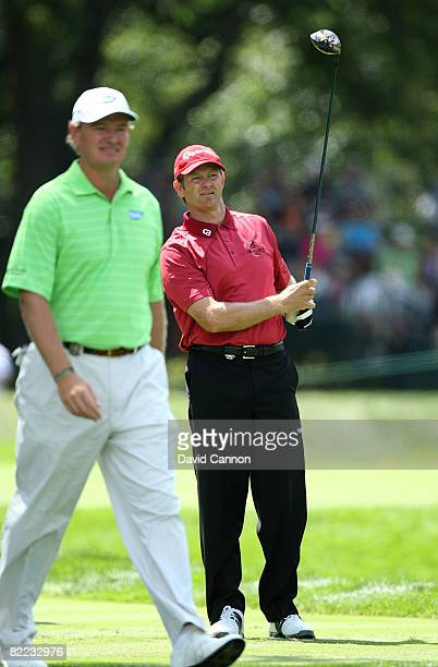 Retief Goosen of South Africa watches his tee shot on the sixth hole while Ernie Els of South Africa passes by during round three of the 90th PGA...