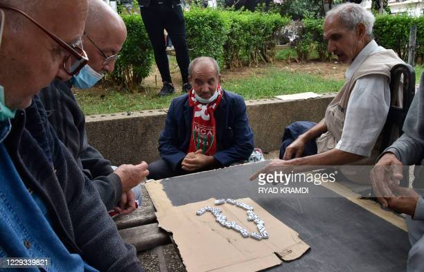 """Retired Algerian men play dominos at the """"Taleb Abderhaman"""" parc in the popular neighbourhood of Bab El-Oued in the capital Algiers on October 26,..."""