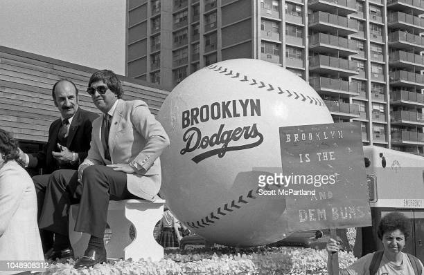 Retired American baseball player Cal Abrams of the Brooklyn Dodgers sits with an unidentified man on his former team's parade float during the...