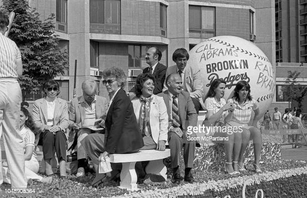 Retired American baseball player Cal Abrams of the Brooklyn Dodgers sits with unidentified others on his former team's parade float during the...