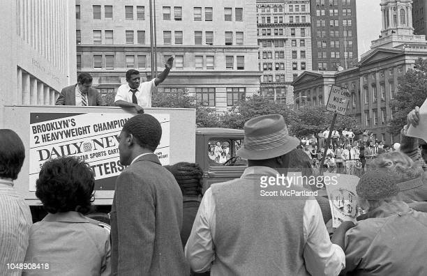Retired American heavyweight boxer Floyd Patterson waves as he rides in a New York Daily News truck during the Brooklyn Bridge's 100th birthday...