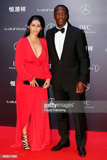 Retired American sprinter Michael Johnson poses with his wife on the red carpet for Laureus World Sports Awards ceremony at the Grand Theater on...