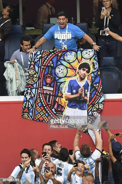 Retired Argentina forward Diego Maradona carries a poster bearing his portrait ahead of the Russia 2018 World Cup Group D football match between...