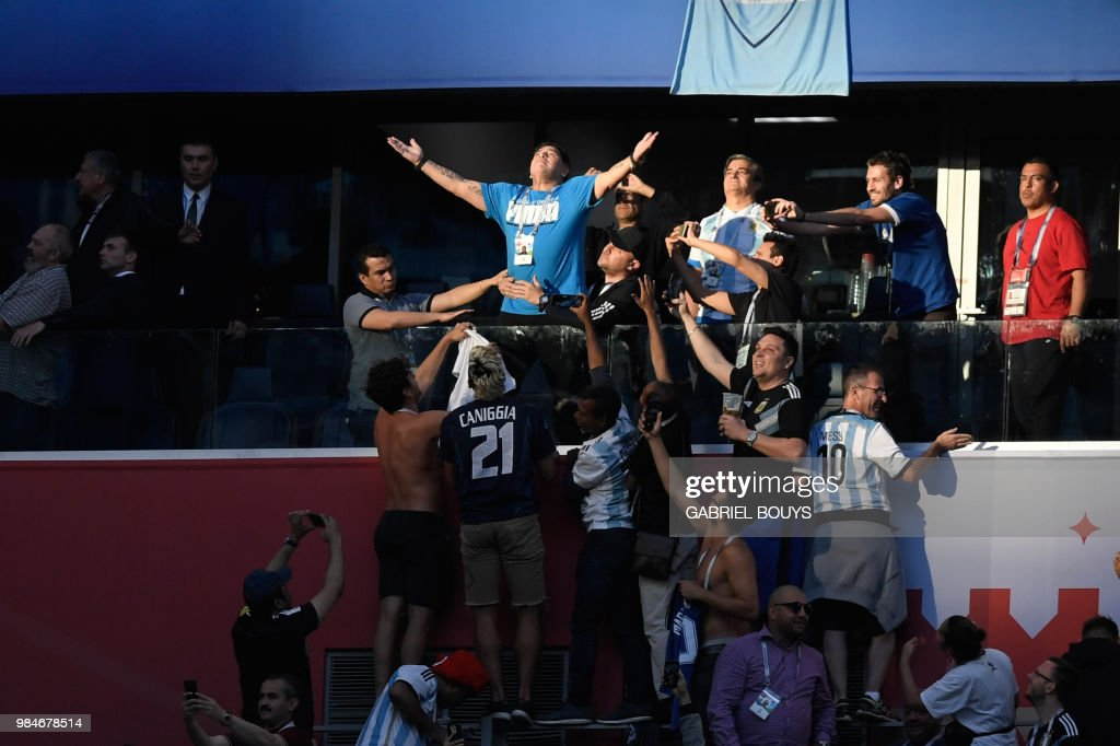 TOPSHOT - Retired Argentina forward Diego Maradona (top C) reacts before the Russia 2018 World Cup Group D football match between Nigeria and Argentina at the Saint Petersburg Stadium in Saint Petersburg on June 26, 2018. (Photo by GABRIEL BOUYS / AFP) / RESTRICTED