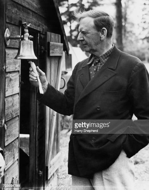 Retired British Admiral Sir Noel Laurence ringing a bell to call workers to a meal at a farm workers' camp near Woodhatch in Surrey 28th April 1943...