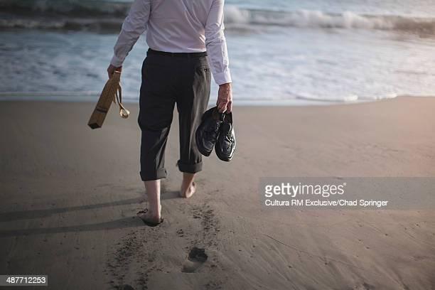 retired businessman carrying shoes and tie, strolling to sea - sint maarten nederlands gedeelte stockfoto's en -beelden