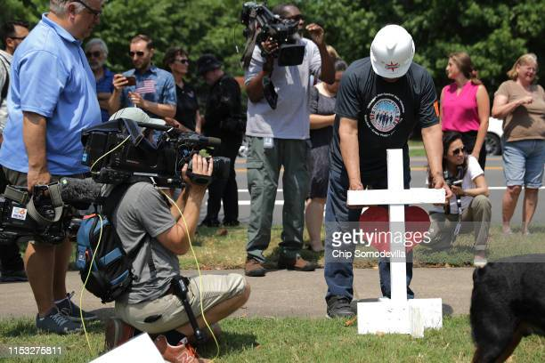 Retired carpenter Greg Zanis of Aurora Illinois places one of his handmade crosses for the 12 victims of a mass shooting at a makeshift memorial at...