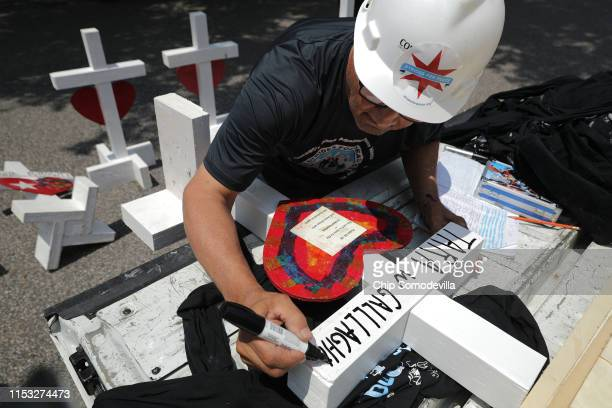 Retired carpenter Greg Zanis of Aurora Illinois writes the name of the 12 victims of a mass shooting onto his handmade wood crosses before placing...