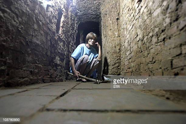 Retired Chinese coal miner Chen Xinnian shows off his underground home he carved beneath the shack he lives in Zhengzhou, central China's Henan...