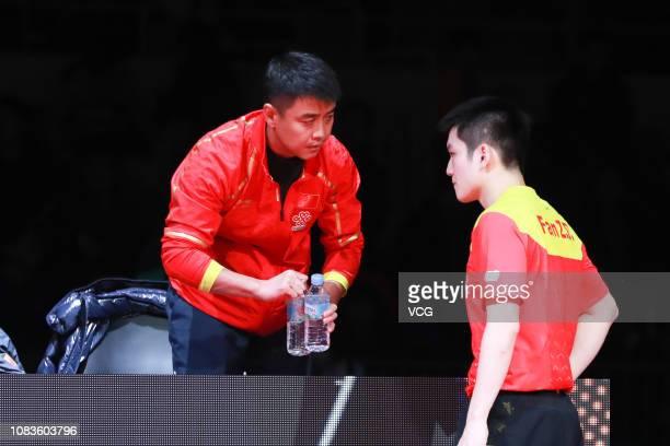 Retired Chinese table tennis player Wang Hao talks with Fan Zhendong of China during the Men's Singles Quarterfinals against Hugo Calderano of Brazil...