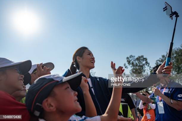 Retired Chinese tennis player Li Na takes a selfie with children fans during the 'Kids Participation Day' in Prudential Hong Kong Tennis Open 2018 on...