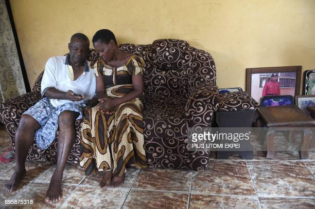 Retired civil servant Sunday Otoide and his wife Grace look at cell phone pictures of their children residing in Italy in their flood damaged...