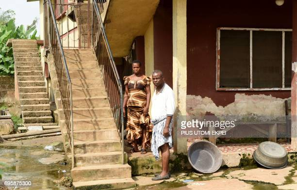 Retired civil servant Sunday Otoide poses for a photograph along with his wife Grace in their flood damaged compound in Benin City capital of Edo...