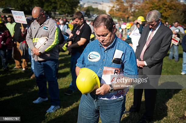 Retired coal miner Robert Tilley of West Virginia and Sen Rob Portman ROhio right bow their heads in prayer during the 'Stand up for American Energy...
