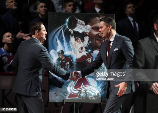Retired Colorado Avalanche player Milan Hejduk is presented with a painting by Josh Kroenke during a ceremony to retire Hejduk's number prior to the...